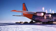 VX-6 C-130 BL unloading fuel drums while moving forward on skis.  Beardmore Weather Station.
