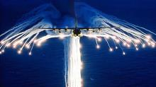 A C-130 H dispensing heat flares for protection against missiles.